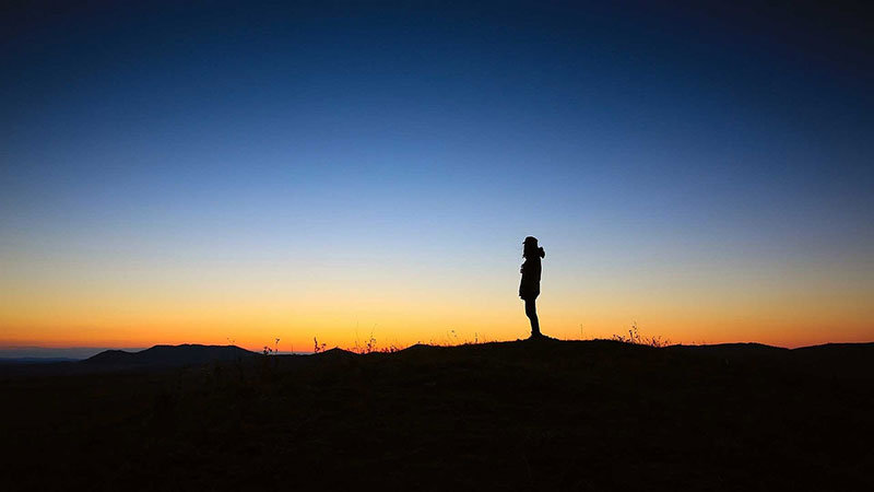 Silhouette of a lone hiker at sunset