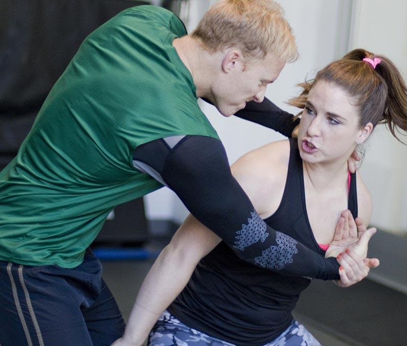 Man and woman practicing Krav Maga choke defense technique