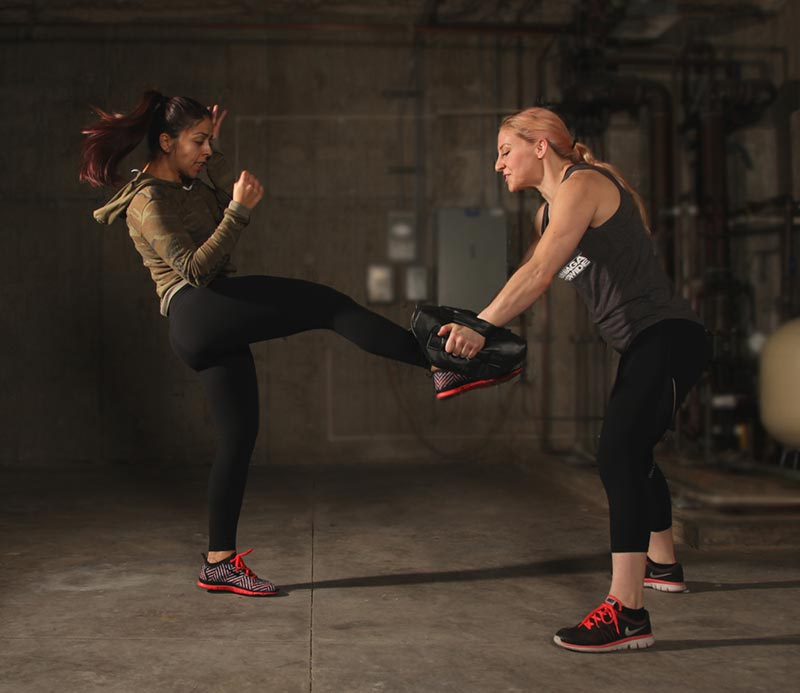 Self-defense techniques: Two women practicing Krav Maga groin kick