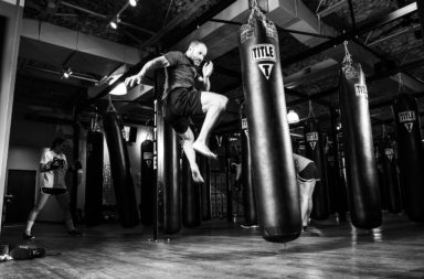 Self-defense - man kicking heavy bag in a gym