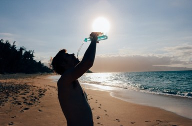 Man Drinking Water on a Beach