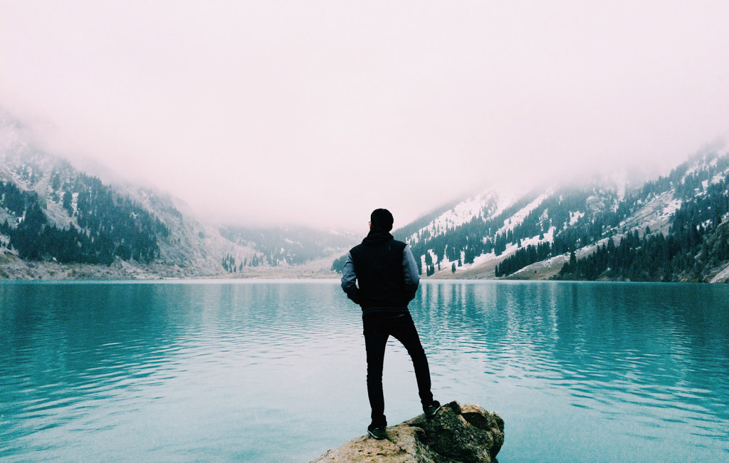 Man Standing Near a Mountain Lake
