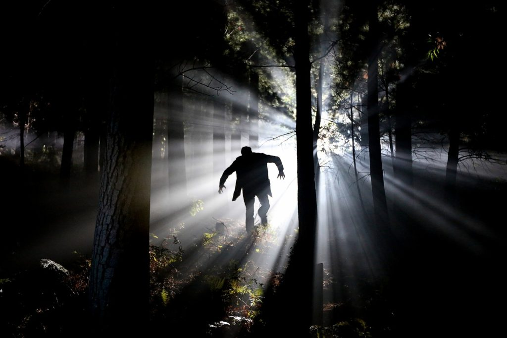 Eerie silhouette running in forest